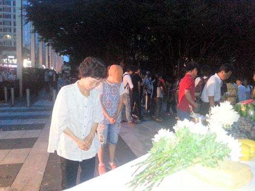 지난 23일 서초동 삼성본관 건물 앞에서 열린 고(故) 황민웅씨 7주기 추모제에서 용산참사 희생자 고(故) 이상림씨의 부인인 전재숙(68)씨가 헌화한 뒤 묵념하고 있다.