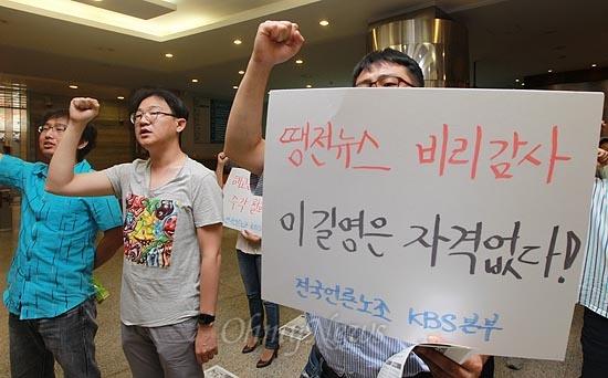 """KBS 새노조 조합원들이 31일 정오 서울 여의도 KBS 사옥 '민주의 터'에서 '비리인사 추천 철회와 부당징계 분쇄를 위한 긴급기자회견'을 열고 이길영 현 감사의 차기 KBS 이사 선임을 철회할 것을 촉구하며 구호를 외치고 있다. 이날 95일 동안 파업을 벌였던 조합원들은 복귀 이후 53일만에 첫 집회를 열고 """"이길영 감사는 온갖 부정부패 의혹에 휩싸인 인물이며 지난 2008년 대구경북 한방산업진흥원 원장으로 재직 당시 친구 아들을 부당한 방법으로 채용했다가 감봉 3개월의 징계를 당한 인물이다""""고 주장했다."""