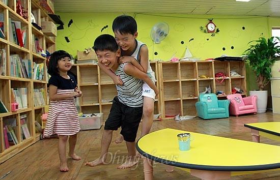 13일 오후 서울 동작구 상도동 성대골 마을학교에서 황서준이 알까기 놀이에 져서 업고 뛰기 벌칙을 수행하고 있다.