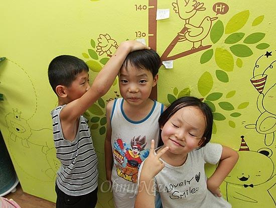 13일 오후 서울 동작구 상도동 성대골 마을학교에서 아이들이 서로 키를 재고 있다. 벽면에 그려진 그림은 마을 어머니들이 손수 디자인하고 페인트로 색칠해 꾸며놓았다.