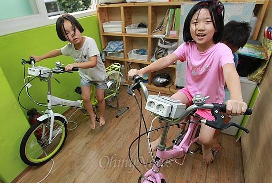 13일 오후 서울 동작구 상도동 성대골 어린이 도서관에서 어린이들이 페달을 돌려 전기를 만드는 자전거 발전기를 타고 놀고 있다. 성대골 마을은 '에너지 자립마을'로 배움을 실천으로 이어가고 있다.