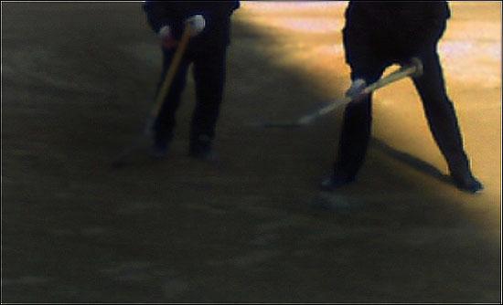 한 학교 주무원 2명이 운동장 평탄화 작업 중이다.