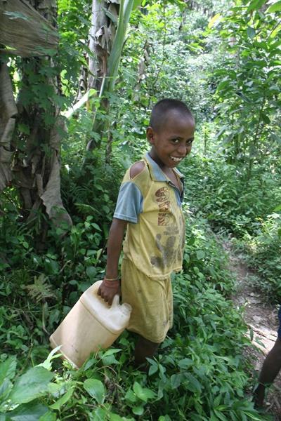 5L 물통에 식수를 담아 맨발로 2시간 산길을 걸어 집에 돌아오는 동티모르 아수마노 마을 아이. 인도네시아 식민지 시절, 토벌군이 진입하기 어려워 독립군의 은신처였던 산간 오지로 주민 70% 이상이 한 두 시간 떨어진 산간 식수원에서 물을 길어온다. 주로 아이들이 도맡아 하고 있다. 통티모르는 2011년 국민의 37.4%가 국제빈곤선인 1일 $1.25 이하의 삶을 연명한다.