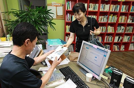 4일 오후 서울 강북구 수유마을시장 골목 한쪽에 위치한 '작은도서관'에서 이재권 도서관 관장이 책을 빌리러 온 주민에게 대여해 주고 있다.