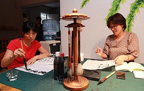 전민정 수유마을시장 프로젝트 매니저(오른쪽)와 주민이 4일 오후 서울 강북구 수유마을시장 내 주민문화공간인 '다락방'에서 열린 서예 모임에 참석해 붓글씨 쓰기 연습을 하고 있다.