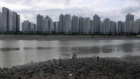 새로 생긴 거대한 신도시 아파트와 포구의 풍경이 묘한 대조를 이룬다.