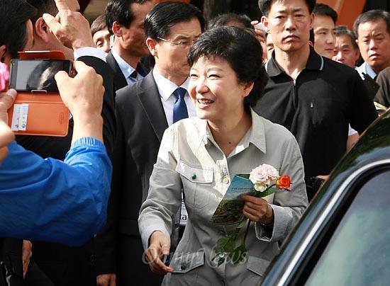 박근혜 새누리당 대선후보가 11일 오후 서울 잠실실내체육관에서 열린 제65회 전국농촌지도자대회에 참석한 뒤 부근에 마련된 농산물 홍보부스에서 받은 꽃을 들고 행사장을 떠나고 있다.