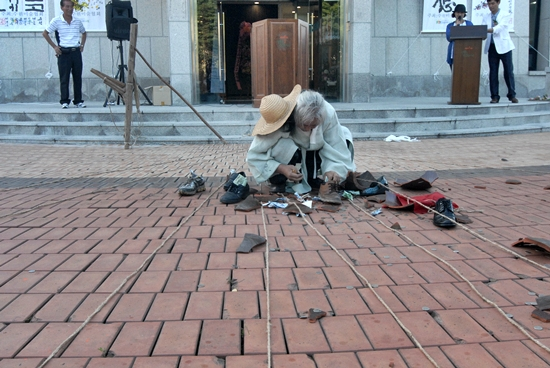 해위예술 깨진 독 안에 있던 신발에 돈을 줏어 넣고 있다. 뒤편 우측 연단에 서 있는 사람이 나레이션을 맡은 권미강이다.