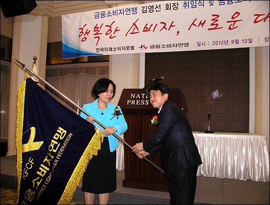 12일 금융소비자연맹 4대 회장에 취임한 김영선 전 새누리당 의원(왼쪽)이 이성구 전 회장에서 단체 깃발을 인수하고 있다.