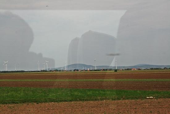 열차 창으로 보이는 오스트리아 들판 저 멀리 풍력 발전기가 보이고 잘 정돈된 느낌이 드는 오스트리아 들판