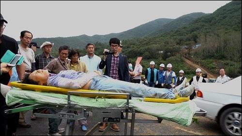 쓰려져 실신한 주민 시공사 측 인부들에 들려 내동댕이쳐져 실신한 한 주민이 들것에 실려 구급차로 급히 호송되고 있다. 이분은 청도의 한 병원 읍급실로 옮겨졌으나, 정밀 진단을 위해 큰 병원으로 이송되었다.