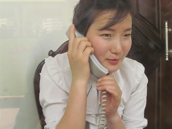 두 손으로 공손히 손님의 전화를 받는 식당의 종업원