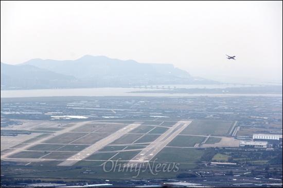 신어산에서 바라본 김해공항 활주로 전경. 낙동강 하구언이 멀리 보인다.