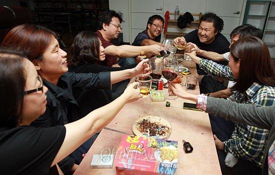 """아이들이 잠든 밤 어른들의 잔치가 시작된다. 서울 마포구 성미산자락에 공동주택을 꾸려 살고 있는 왕자(이승현), 맥가이버(강석필), 뚝이(고창석), 토끼(우연창) 부부가 추석연휴를 하루 앞둔 지난 9월 29일 오후 공동주택 지하1층 공동작업실에서 함께 술잔을 부딪히고 있다. """"오가는 게 귀찮아서 함께 산다""""는 이들에겐 서로의 삶을 나눌 수 있는 이런 술자리가 공동주택을 꾸려가는 원동력으로 작용한다."""