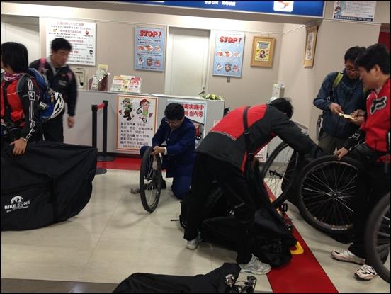 일본 세관 직원이 자전거 바퀴를 모두 닦고 있다
