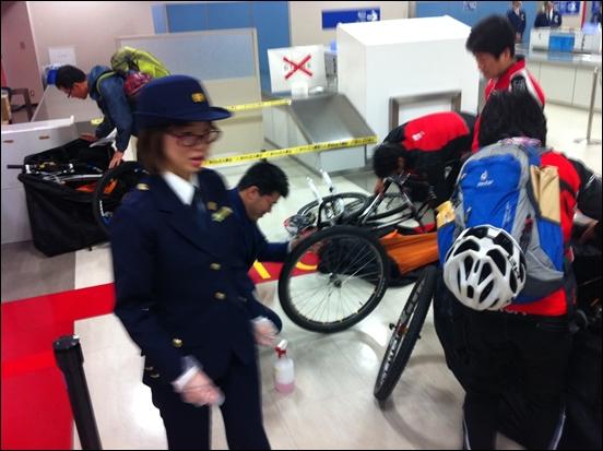 일본 세관에서 분리된 자전거를 조립하고 바퀴를 닦고 있다