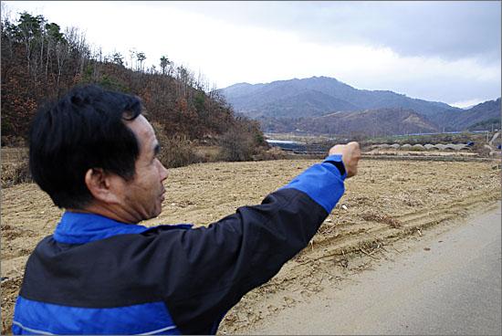 서정호씨가 손가락이 잘려나가 뭉툭한 손으로 아직도 지뢰가 묻혀 있는 마을 주변의 야산을 가리키고 있다.