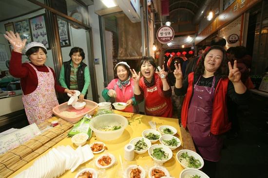 남문시장 진흥조합의 여성상인회 회원들이 먹거리 장터에서 국수를 준비하며 촬영을 위해 활짝 웃고 있다.
