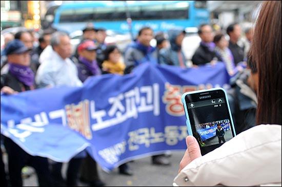'전태일 열사 정신 계승! 2012 전국노동자대회'에 참가한 민주노총 노조원들이 서울역까지 행진을 펼치고 있는 가운데 한 외국인이 스마트폰을 이용해 노동자들의 행진모습을 사진 찍고 있다.