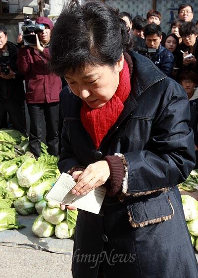 박근혜 새누리당 대선후보가 12일 오후 전북 익산 금마시장을 방문해 미나리를 구입한 뒤 지갑에서 지폐를 꺼내고 있다. 박 후보가 주머니에서 꺼낸 지갑에는 신용카드나 신분증은 없이 지폐만 몇장 들어있다.