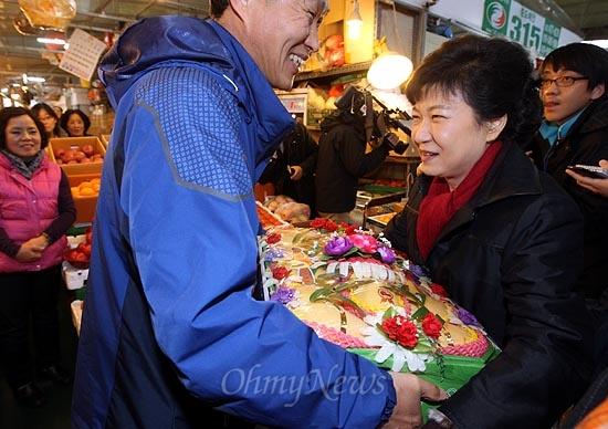 박근혜 새누리당 대선후보가 13일 오후 대전광역시 유성구 노은농수산물도매시장에서 한 상인으로부터 과일을 선물받고 있다.