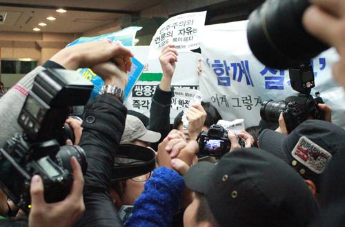박근혜 후보가 토크콘서트 행사장에 입장한 뒤 <노동자 연대 대학생 그룹> 소속 학생들과 쌍용차 해고노동자들이 사복경찰에 밀려나며 구호를 외치고 있다.