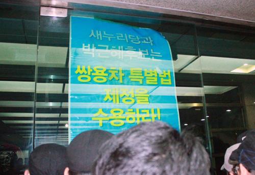 사복경찰에 의해 건물 밖으로 밀려난 <노동자 연합 대학생 그룹> 소속 학생들과 쌍용차 해고노동자들이 유리문을 통해 피켓을 들고 농성을 벌이고 있다.