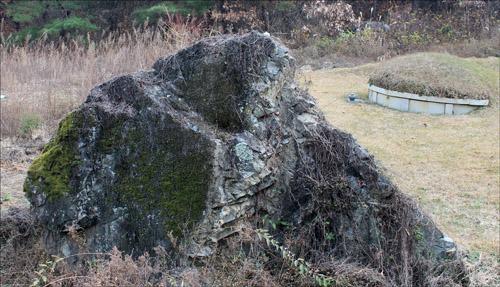 상계1리 칠성고개로 넘어가는 길목에서 본 고인돌 중 하나. 청동기 시대의 무덤 뒤로 현대의 묘소가 보인다.