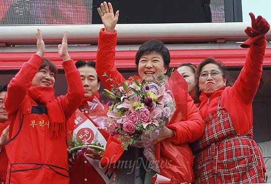 박근혜 새누리당 대선후보가 30일 오후 부산 진구 부전시장을 찾아 상인들로부터 꽃다발을 건네받고 유권자들에게 지지를 호소하며 손을 흔들어보이고 있다.