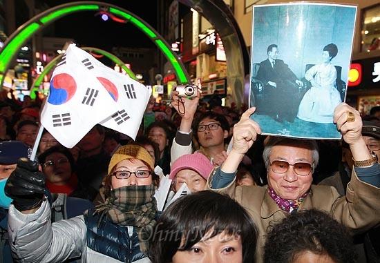 박근혜 새누리당 대선후보가 30일 오후 부산 중구 피프광장에서 유세를 펼치자, 한 지지자가 박정희 전 대통령과 육영수씨의 사진을 들어보이고 있다.