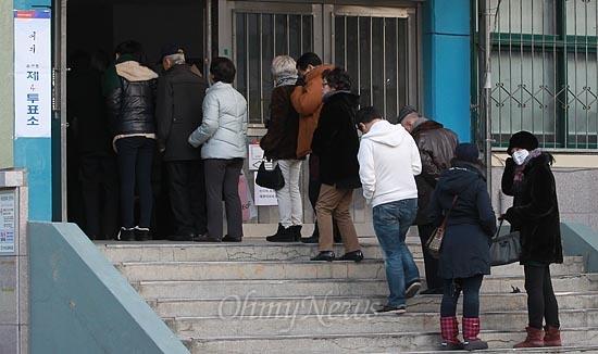 제18대 대통령선거 날인 19일 오후 서울 영등포구 여의도중학교에 마련된 여의도 제4투표소에서 유권자들이 투표를 하기 위해 건물 밖까지 길게 줄을 서서 기다리고 있다.