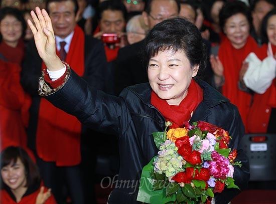 제18대 대통령선거에서 당선이 확실시 되고 있는 박근혜 새누리당 대선후보가 19일 오후 서울 여의도 당사에 마련된 선거종합상황실에서 축하꽃다발을 건네받은 뒤 손을 들어보이고 있다.