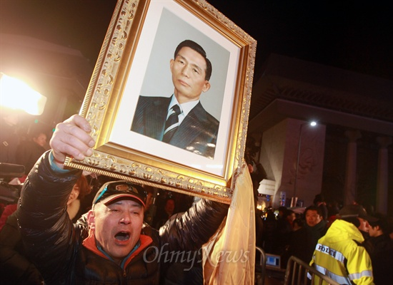 제18대 대통령선거가 치뤄진 19일 오후 박근혜 새누리당 대선후보 당선이 확정적인 가운데 서울 광화문광장에서 한 지지자가 박 후보 아버지인 박정희 전 대통령의 사진을 들고 나와 감격해 하고 있다.