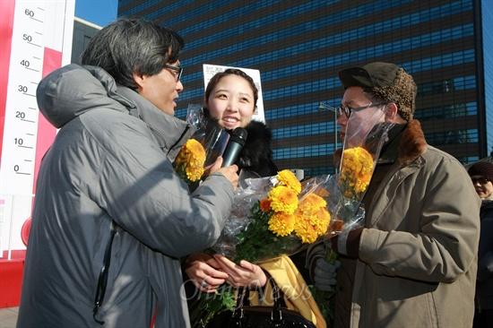 <오마이뉴스> 생방송 '힐링올레'의 오연호 대표기자와 서해성 작가가 24일 오후 서울 광화문광장에서 노란국화를 준비한 시민과 인터뷰를 하고 있다.