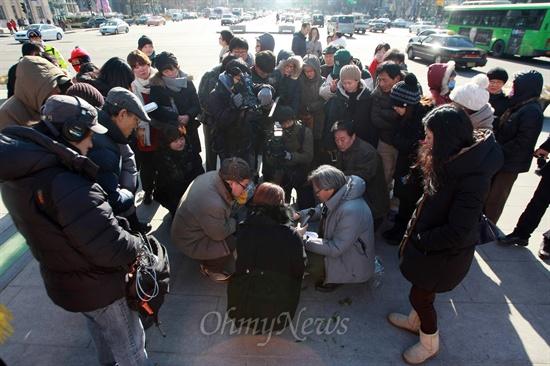 <오마이뉴스> 생방송 '힐링올레'의 오연호 대표기자와 서해성 작가가 24일 오후 서울 광화문광장에서 시민들과 함께  지난 17일 워싱턴에서 온 소포의 내용물을 확인하고 있다.