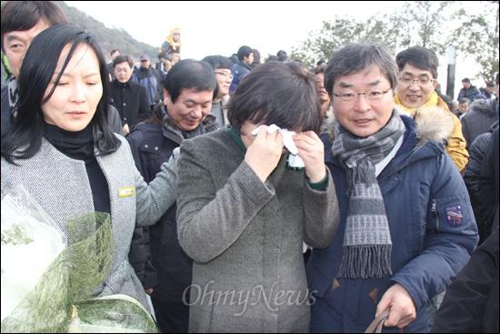 노무현재단은 1일 김해 봉하마을 고 노무현 대통령 묘역에서 '계사년 신년 합동 참배' 행사를 열었다. 사진은 참배를 마친 뒤 문재인 의원 부인 김정숙씨가 시민들로부터 인사와 꽃다발을 받은 뒤 눈물을 훔치고 있는 모습.