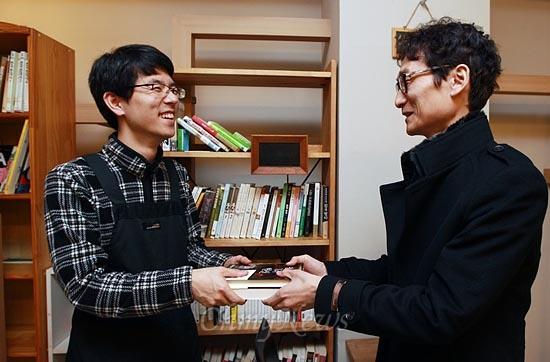15일 오후 서울 서초구 서초동 남부터미널 인근에 위치한 협동조합 카페 '카페 오공'에서 재능나눔에 참가한 홍용호씨가 카페 매니저 조정훈씨에게 책을 기증하고 있다.
