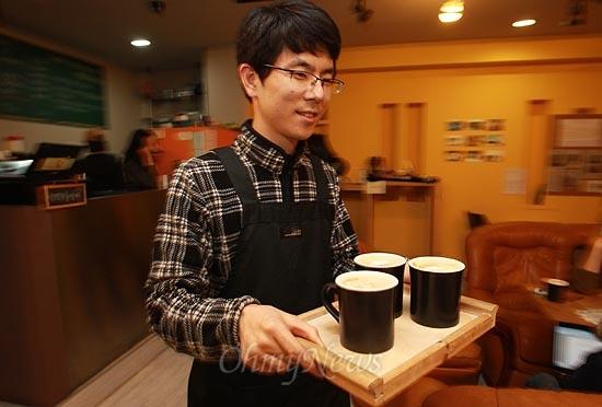15일 오후 서울 서초구 서초동 남부터미널 인근에 위치한 협동조합 카페 '카페 오공'에서 카페 매니저 조정훈씨가 손님이 주문한 음료를 나르고 있다.