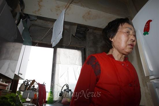 서울 성북구 정릉스카이아파트에서 30년 넘게 산 노복순(78) 할머니. 싱크대 위 벽지는 벗겨져 축 늘어져 있고 그 사이로 시뻘겋게 녹슨 철근이 보이고 있다. 벗겨지지 않은 벽지라도 곳곳에 빗물 자국이 보이거나 곰팡이가 슬어 있다.