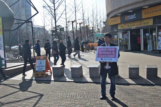 2일 오전, 이마트 고덕점 앞에서 1인시위를 하고 있는 박병호씨 뒤로 시민들이 이마트 안으로 들어가고 있다.