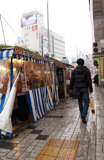 컵밥 노점상이 들어서있는 노량진 길거리. 노점상에서 컵밥을 먹고 있는 사람도 보인다.