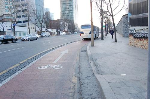 자전거 전용차로 위의 경찰 버스 경복궁 앞 길, 광화문 방향. 자전거 도로 위의 경찰 버스는 사진을 찍은 시점부터 한 시간 뒤에도 여전히 자리를 지키고 있었다. 현행 법으로 이를 처벌할 수 있거나 주정차 금지를 강제할 수 있는 법이 없다.