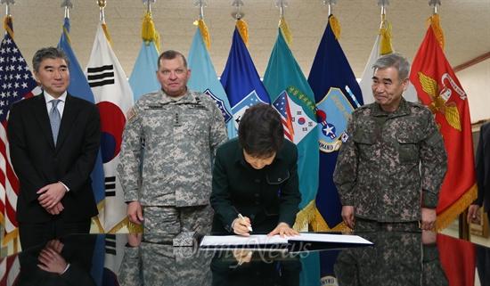 박근혜 대통령 당선인이 22일 오전 서울 용산 한미연합군사령부에 방문한 뒤 방명록을 적고  있다.  권오성 한미연합사 부사령관(박당선인 오른쪽), 제임스 서먼 한미연합사 사령관(박당선인 왼쪽)