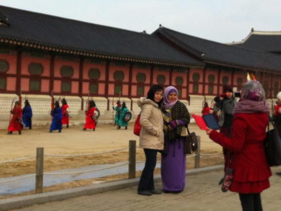 외국인 관광객들이 한국의 대표적인 관광지인 경복궁에서 기념사진을 찍고 있다.