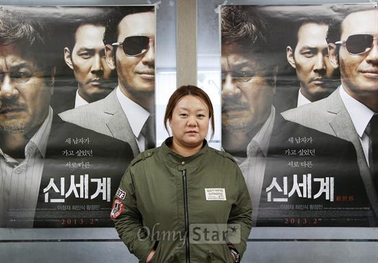 영화<신세계>의 박민정 프로듀서가 25일 오후 서울 신사동에서 오마이스타와 인터뷰에 앞서 영화포스터를 배경으로 포즈를 취하고 있다.