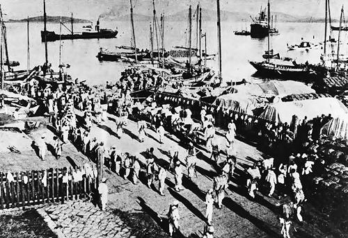 일제강점기 군산항. 부두 노무자들이 쌀을 배에 옮겨 싣고 있다.