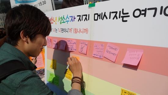 27일 대한문 앞에서 열린 고 육우당 10주기 추모 거리캠페인에 참여한 학생이 청소년 성소수자 지지에 대한 메시지를 남기고 있다.