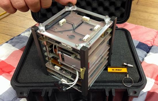 송씨가 쏘아올린 인공위성 오픈샛(Open Sat). 고휘도 LED와 통신모듈, 태양광 충전 시스템 등이 탑재됐다. 오른쪽에 있는 열쇠고리는 로켓 발사 직전에 발사체에 부착된 인공위성에서 뽑아내는 장치다. S-RBF는 Satelite-Remove Before Fire의 약자.