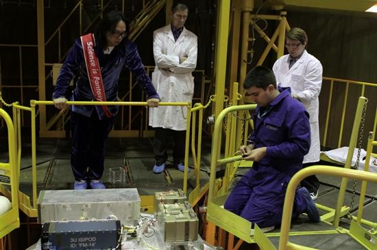프랑스 인공위성 발사업체 노바나노 직원들이 4월 19일 카자흐스탄 바이코누르 우주기지에서 발사된 러시아 인공위성 Bion-M1 위에 송호준씨의 인공위성을 부착하고 있다. 좌측 붉은 띠를 두른 사람이 송씨.
