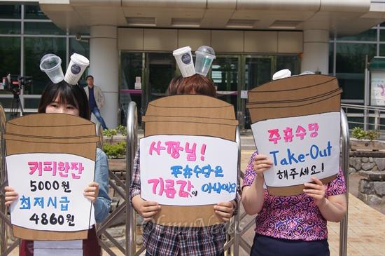 회원들이 커피전문점에서 최저임금법 위반과 주휴수당 미지급에 대해 항의하는 손피켓을 들고 있다.